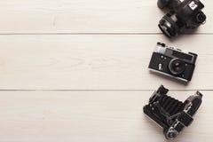 在白色桌上的三台不同照相机 免版税图库摄影