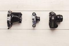 在白色桌上的三台不同照相机 免版税库存照片