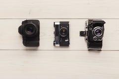 在白色桌上的三台不同照相机 图库摄影