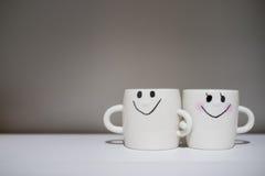 在白色桌上的两个可爱的杯子 关于关系和l的概念 库存图片