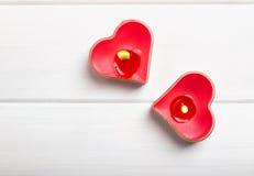在白色桌上的两个红色心形的蜡烛, 免版税库存图片