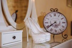在白色桌上的典雅的新娘鞋子 免版税库存图片