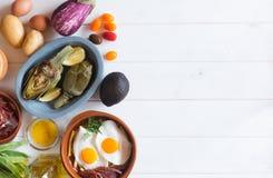在白色桌上的有机食品 朝鲜蓟和柠檬在板材 鸡蛋油煎了蔬菜 这产品人民 免版税图库摄影