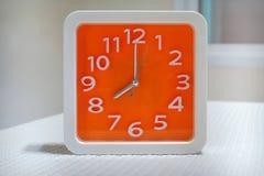 在白色桌上的橙色壁钟 库存图片