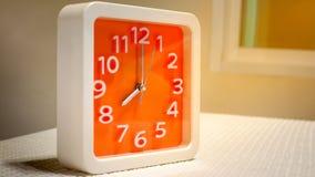 在白色桌上的橙色壁钟 免版税库存照片