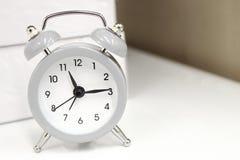 在白色桌上的浅灰色的小闹钟 读秒、最后期限和时间背景 库存图片