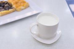 在白色桌上的热的牛奶 免版税库存图片