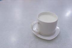 在白色桌上的热的牛奶 库存照片