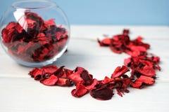 在白色桌上的玫瑰花瓣 库存图片