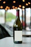 在白色桌上的红葡萄酒瓶 免版税库存图片
