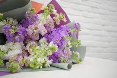 在白色桌上的美丽的可爱的淡紫色花束 免版税库存图片