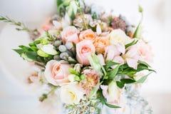 在白色桌上的美丽的现代婚礼花束 免版税库存图片