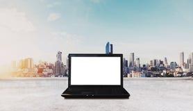 在白色桌上的计算机膝上型计算机,有曼谷市视图在日出背景中 裁减路线屏幕 免版税库存照片