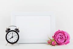 在白色桌上的画框装饰的玫瑰色花大模型和闹钟与文本的空的空间和设计您blogging 图库摄影