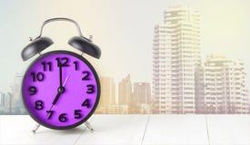 在白色桌上的紫色早晨闹钟与城市 免版税库存照片