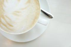 在白色桌上的Cappucino杯子 免版税库存照片