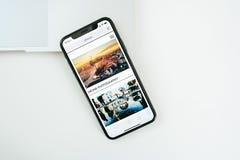 在白色桌安置的新的苹果计算机Iphone x旗舰智能手机 库存图片