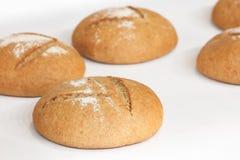 在白色桌布或架子的几圆的新鲜的热的面包在面包店 免版税库存图片
