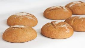在白色桌布或架子的几圆的新鲜的热的面包在面包店 免版税库存照片