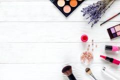 在白色桌有淡紫色顶视图,大模型上的化妆用品 库存照片