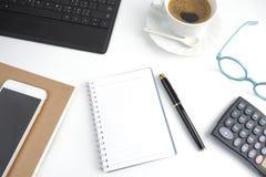 在白色桌面上的空白页笔记本有笔的,咖啡, lapto 免版税库存图片
