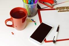 在白色桌面的手机、咖啡和办公室项目 到达天空的企业概念金黄回归键所有权 库存图片