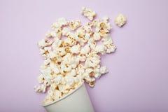 在白色桶的玉米花在桃红色背景 免版税图库摄影
