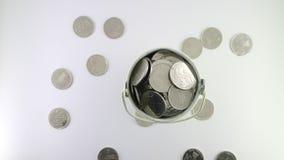 在白色桶的硬币在白色背景 免版税图库摄影