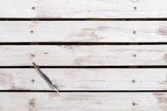 在白色棕色土气木地板上的鸟羽毛 背景舱内甲板位置 免版税库存图片