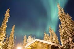 在白色森林和客舱上的北极光 免版税库存照片