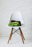 在白色椅子的五颜六色的被编织的美利奴绵羊的羊毛围巾 免版税库存照片