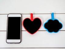 在白色椅子背景的手机与小委员会cloudt和心脏 免版税库存照片