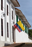 在白色殖民地大厦的哥伦比亚的旗子 库存图片