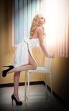 在白色毛巾包裹的年轻白肤金发的妇女看在窗口。有一块毛巾的美丽的少妇在她的在浴以后的身体附近 免版税库存照片