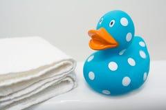 在白色毛巾旁边的逗人喜爱的橡胶鸭子在卫生间关闭 库存图片