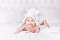 在白色毛巾的可爱婴孩谎言在床上 愉快的童年和医疗保健概念 免版税库存图片