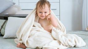 在白色毛巾盖的愉快的快乐的小孩男孩在沐浴以后 库存图片