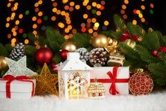 在白色毛皮的圣诞节装饰与杉树分支特写镜头、礼物、xmas球、锥体和其他对象在黑暗的背景与锂 库存图片