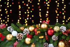 在白色毛皮的圣诞节装饰与杉树分支特写镜头、礼物、xmas球、锥体和其他对象在黑暗的背景,光 免版税图库摄影