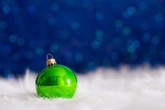 在白色毛皮的绿色圣诞节球与诗歌选在蓝色bo点燃 库存照片