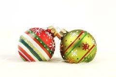 在白色毛皮背景的两个五颜六色的圣诞节球 免版税库存图片