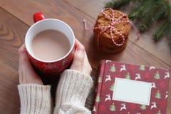 在白色毛线衣的女性手拿着一个红色杯子在木桌上的可可粉 库存照片