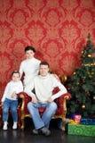 在白色毛线衣的愉快的家庭和牛仔裤临近圣诞树 库存图片