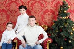 在白色毛线衣的愉快的家庭和牛仔裤临近圣诞树 免版税图库摄影