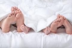 在白色毯子下的滑稽的家庭脚 免版税图库摄影