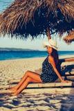 在白色沙子海滩海岛上的日落期间美好女性放松在竹子sunbed 免版税库存照片