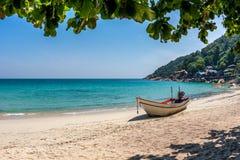 在白色沙子海滩的一条小船热带蓝色海 白天,酸值Phangan,泰国 库存图片