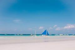 在白色沙子海滩的一条蓝色风船 蓝色多云天空 库存图片
