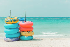 在白色沙子海滩的五颜六色的橡胶环 免版税库存图片