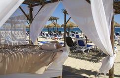 在白色沙子海滩的按摩表 免版税库存照片